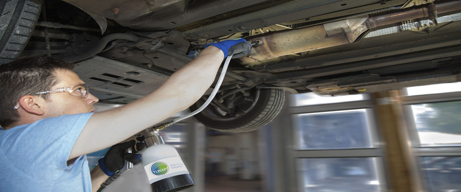 Mechanic under a lifted car using a cup gun with hose and probe to clean a diesel particulate filter
