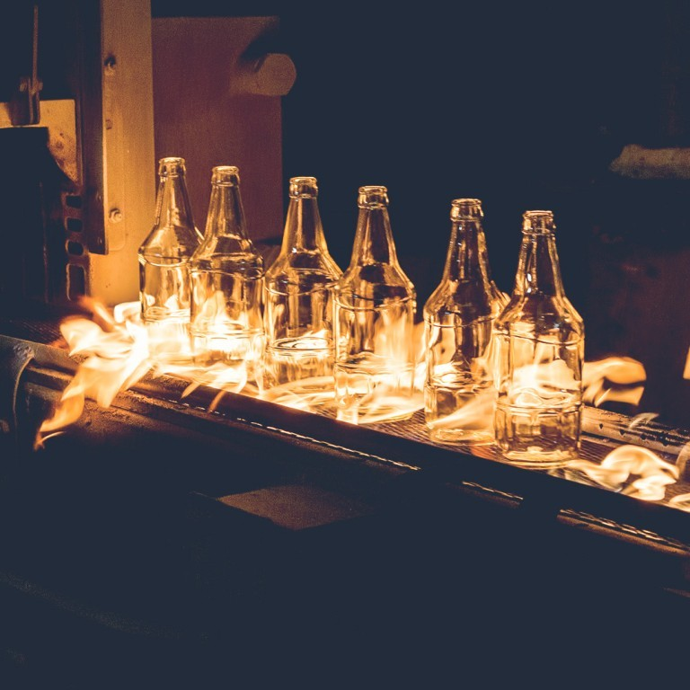 Glowing glass bottles at the production line