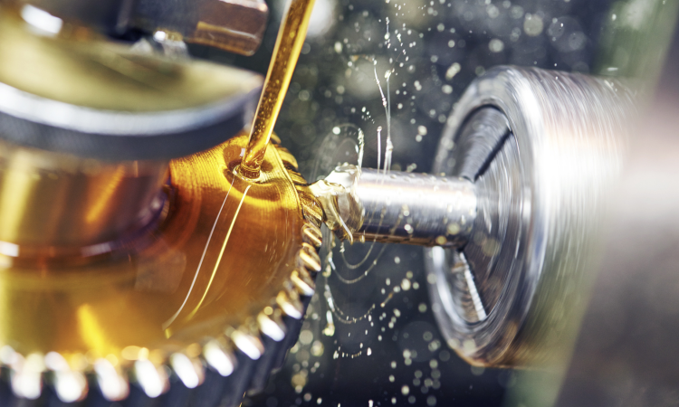 Gold-colored lubrication oil is applied on an industrial component